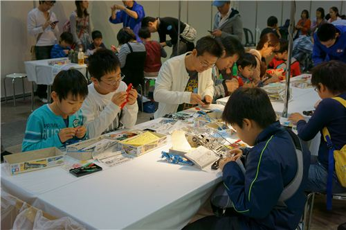 Some children are assembling miniature items